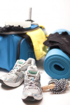 Sport bag with important gym equipment on white ta...
