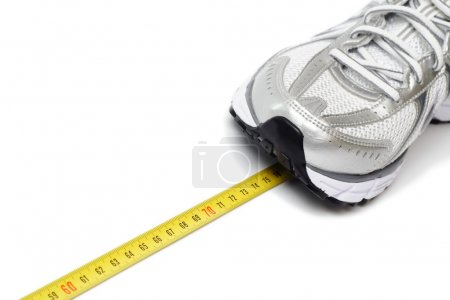 Running shoe and centimeter on white