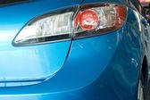 Modern red rear light of a blue car