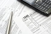 Mobile phone and pen on tax forms