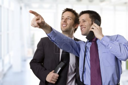 Photo for Young businessman raising his hand and showing something to his colleague - Royalty Free Image