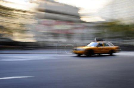 Taxi cab speeding down street in a blur
