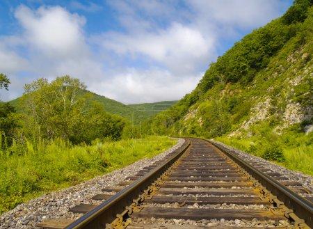 Photo pour Année paysage avec ligne de chemin de fer, collines et ciel nuageux - image libre de droit