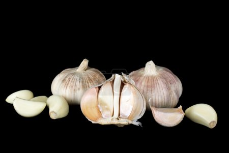 Photo for Garlic bulbs and cloves over the black background - Royalty Free Image