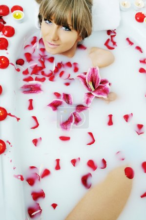 Woman taking bath with flowers