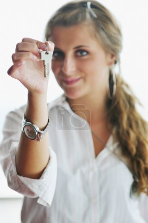 Young woman throwing home keys in air
