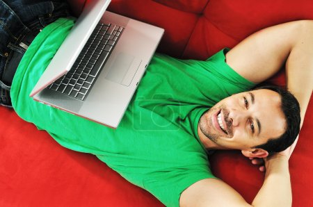 Man relaxing on sofa and work on laptop