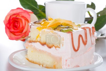 Photo for Piece of cake with fruits rose and cup, isolated on white - Royalty Free Image