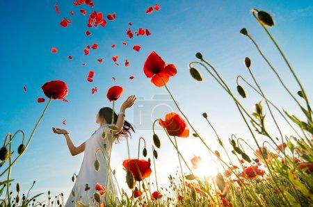 Girl relaxing  in poppy field