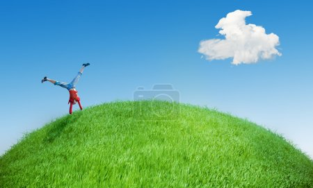 Photo for Young girl do acrobatic feat on the green hill - Royalty Free Image