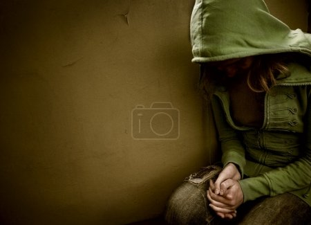 Photo for Teenage girl siting against wall in a depressed state - Royalty Free Image