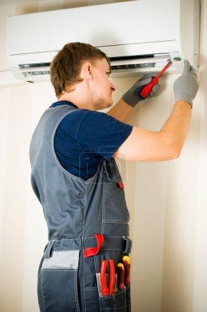 Foto de Un hombre reparación de aire acondicionado - Imagen libre de derechos