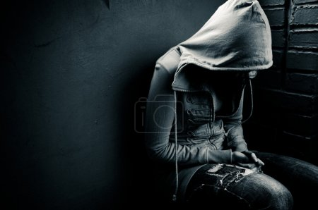 Teenage girl siting against wall in a depressed st...