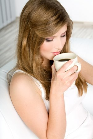 Beautiful woman drinking coffee at bed