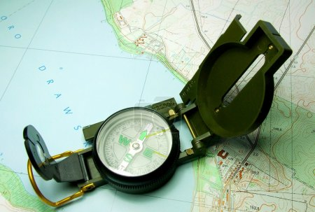 Photo for Open compass lying on map - Royalty Free Image