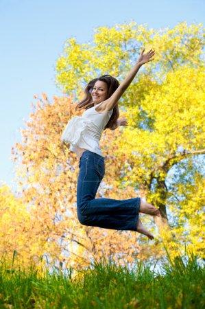 Photo pour Heureuse belle fille sautant de joie sur une journée d'automne - image libre de droit