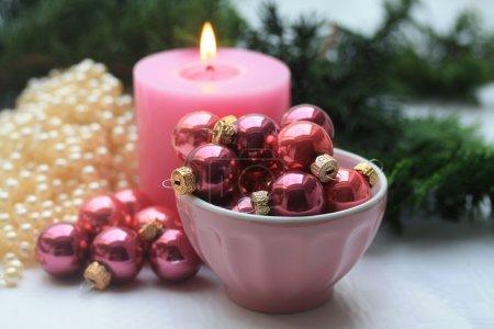 Photo pour Une bougie rose et un bol avec des petites boules de Noël - image libre de droit