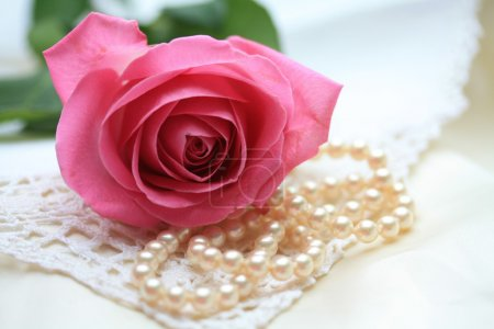 Photo for A pink rose on a pearl necklace and some lace - Royalty Free Image