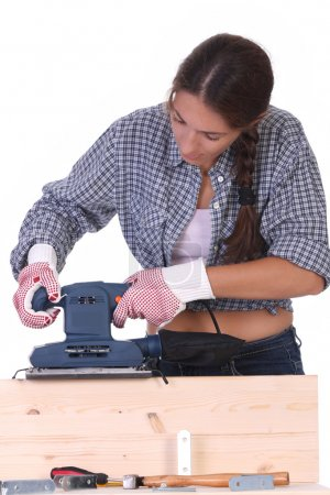 Woman carpenter at work, sander