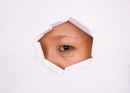 Photo for Eye looking through hole on paper surface - Royalty Free Image