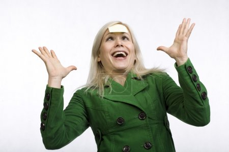 Photo for Busy woman over a white background with sticky note on her head and crazy face expression - Royalty Free Image