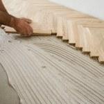Carpenter on work putting wood parquet pieces. Hom...