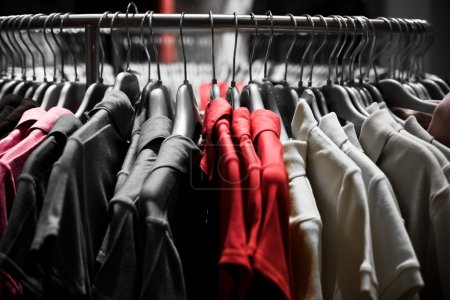 Photo for Clothes hangers with red t-shirts in store ready to choose to buy. Fashion shopping concept - Royalty Free Image
