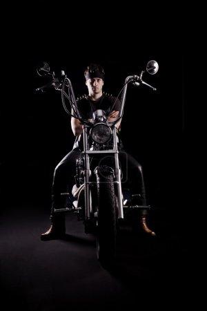 Photo pour Motocycliste sur chopper moto dans le noir. Forte lumière latérale - image libre de droit