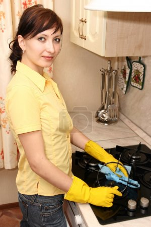 The girl on kitchen wipes an oven