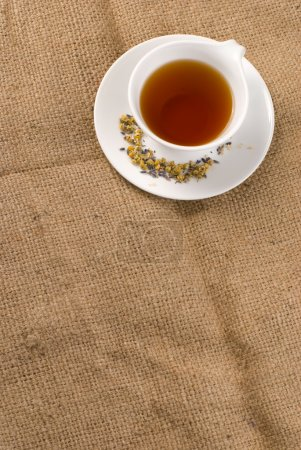 Photo for Red tea in white ceramic cup with burlap background - Royalty Free Image