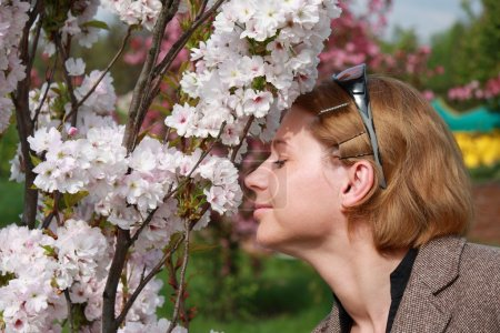 Woman smelling spring flowers outdoors