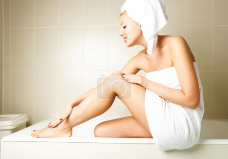 Photo for Beautiful happy woman pampering herself and applying body lotion in the bathroom after the shower - Royalty Free Image