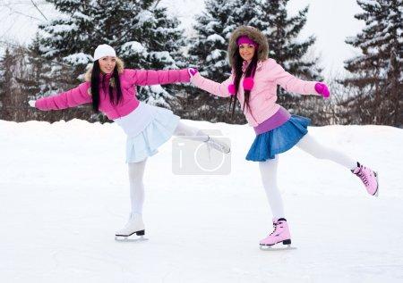 Photo pour Deux belles filles porter chauds vêtements d'hiver patinage sur glace - image libre de droit