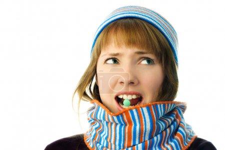 Photo pour Belle fille malheureuse malade avec une tablette dans la bouche isolé sur fond blanc - image libre de droit