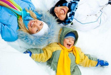 Photo pour Jeunes parents et leur fils portant des vêtements d'hiver chauds se trouvent sur la neige - image libre de droit