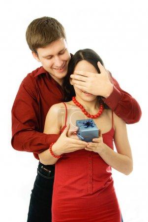 Photo pour Beau jeune homme donne un cadeau à sa femme et ferme les yeux - image libre de droit