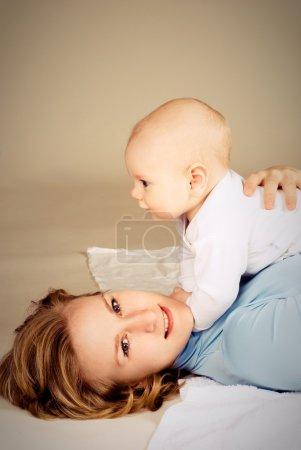Photo pour Heureuse jeune belle maman avec son petit bébé sur le sol - image libre de droit