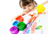 Cute girl painting with finger paints