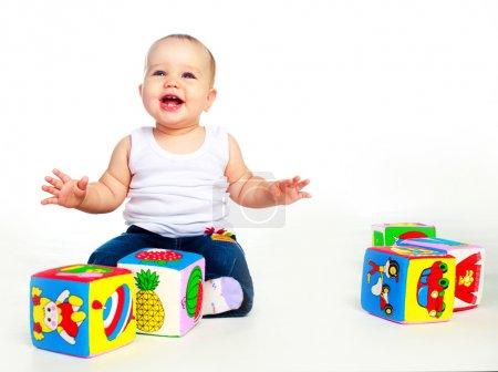 Photo pour Mignon bébé heureux assis sur le sol et jouer avec des jouets - image libre de droit