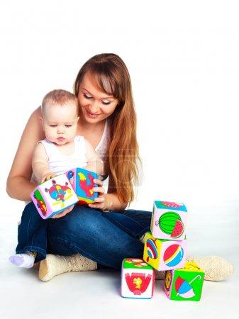 Photo pour Jeune mère et sa fille, assis sur le sol et en jouant avec des jouets - image libre de droit