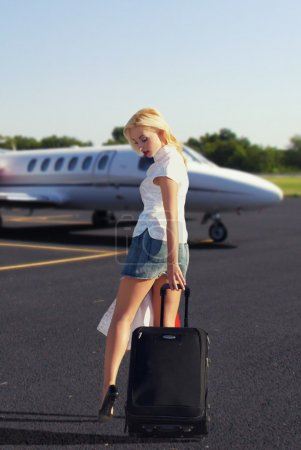 The girl with luggage going to plane