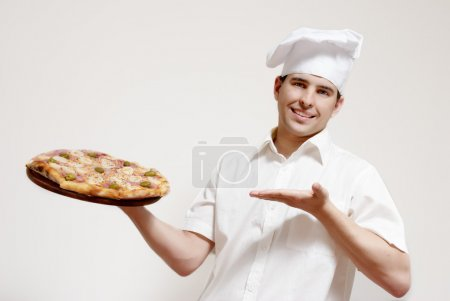 Happy attractive cook with a pizza