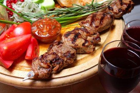 Foto de Shish kebab en un soporte de madera con verduras y especias - Imagen libre de derechos