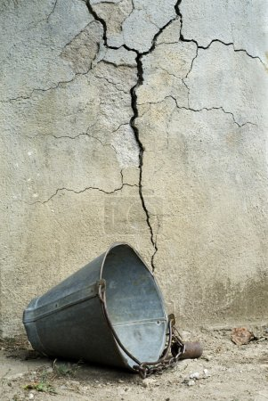 Photo for Old broken scutlle in front of cracked wall of well - Royalty Free Image