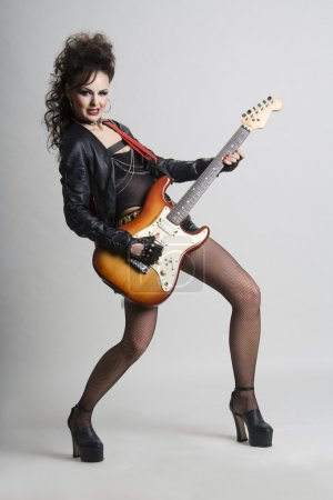 Photo for Beautiful woman playing electric guitar. Shot in studio. - Royalty Free Image