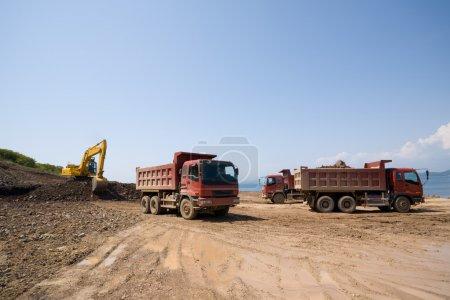 Construction of new seaport. Excavator loads a dum...