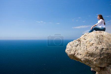 Photo pour Jeune femme assise sur le rocher près de la mer - image libre de droit