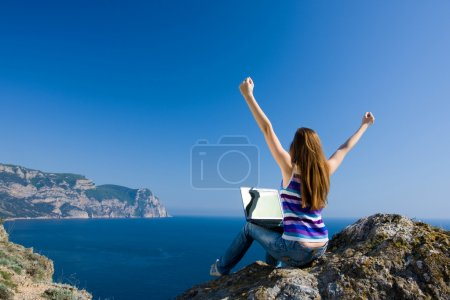 Photo for Woman sitting on the rock with laptop near the sea - Royalty Free Image