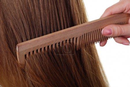 Photo pour Beaux cheveux longs bruns et peigne en bois - image libre de droit
