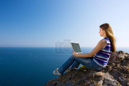 Photo pour Femme assise sur le rocher avec ordinateur portable près de la mer - image libre de droit